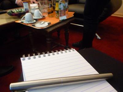 Spiralblock und Füller, im Hintergrund sind Couchtisch mit Tassen und Getränken und Sitzgelegenheiten auf tiefrotem Teppichboden zu sehen.