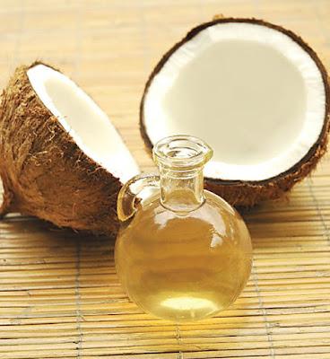 szklany dzban z olejem, połówki kokosa