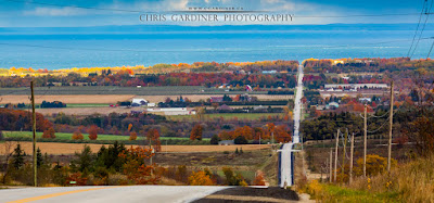 Photo of a beautiful stretch of straight road in autumn and massive Georgian Bay in the background by chris gardiner photography, ontario canada
