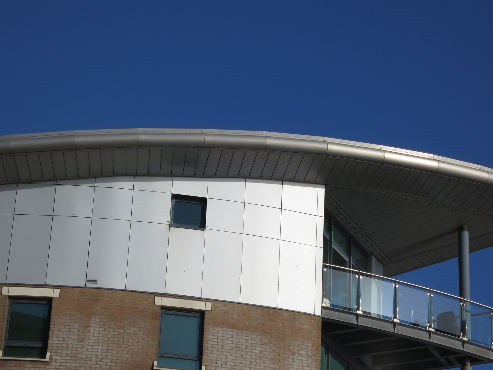 Glass balcony and curved roof against blue sky