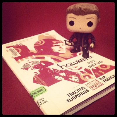 A bobbleheaded figure of Clint Barton, a blond white guy wearing a black and purple leather superhero outfit, stands on a trade paperback copy of Rio Bravo. The book's cover features several people, most of them visibly coded as male, portrayed in vectorish designs of red, orange, and white. Bullseyes liberally adorn the image. Book and figure alike appear in a sea of red.