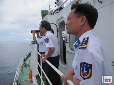 Các chiến sĩ cảnh sát biển sử dụng ống nhòm quan sát những chiếc tàu cá lạ từ xa.