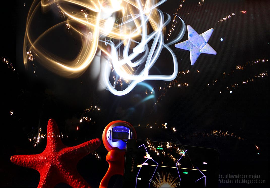 Una estrella de mar, un reloj robot, una estrella fuorescente, un móvil Samsung Galaxy con la app Sky Map, una linterna moviendose en la oscuridad y la foto de un cielo estrellado y unos fuegos artificiales vista en un mac, dan este resultado