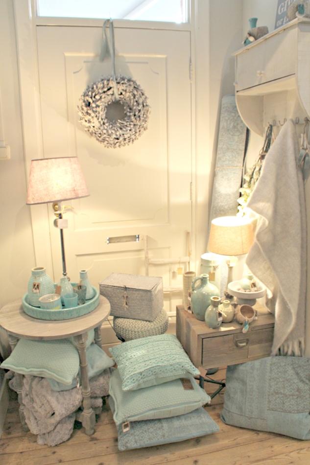 Deko vor einer weißen Kassettentür mit türkisen Kissen und Vasen sowie Lampen