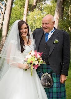 The bride poses with her father before the ceremony