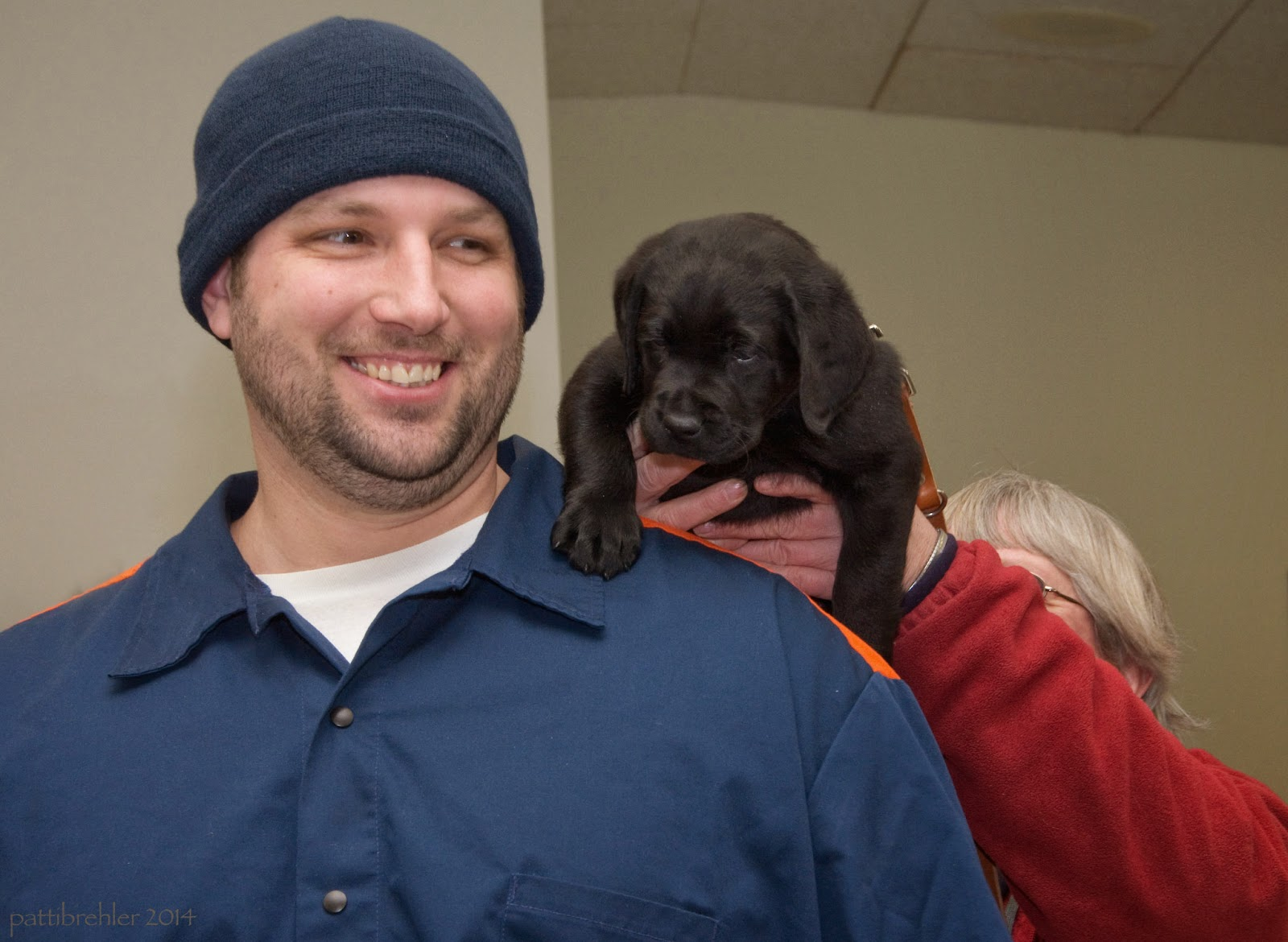 The tall man has his eyes open now and is still smiling. The woman behind him is lifting a small black lab puppy over his left shoulder. The puppy's right paw is on the man's shoulder.