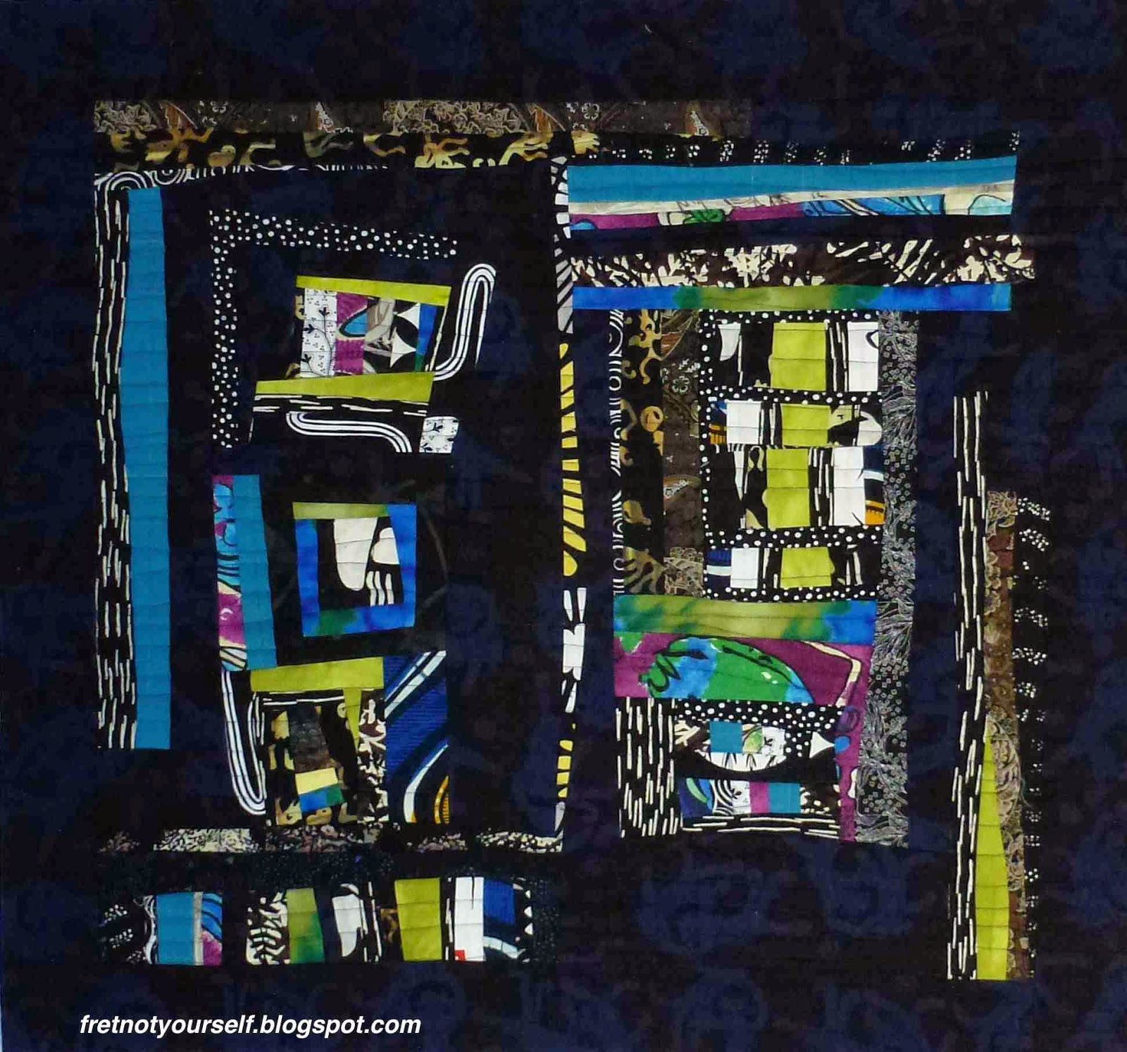 Blue, black, white, chartreuse and yellow fabrics are pieced into a blue-black batik to make this small quilt.