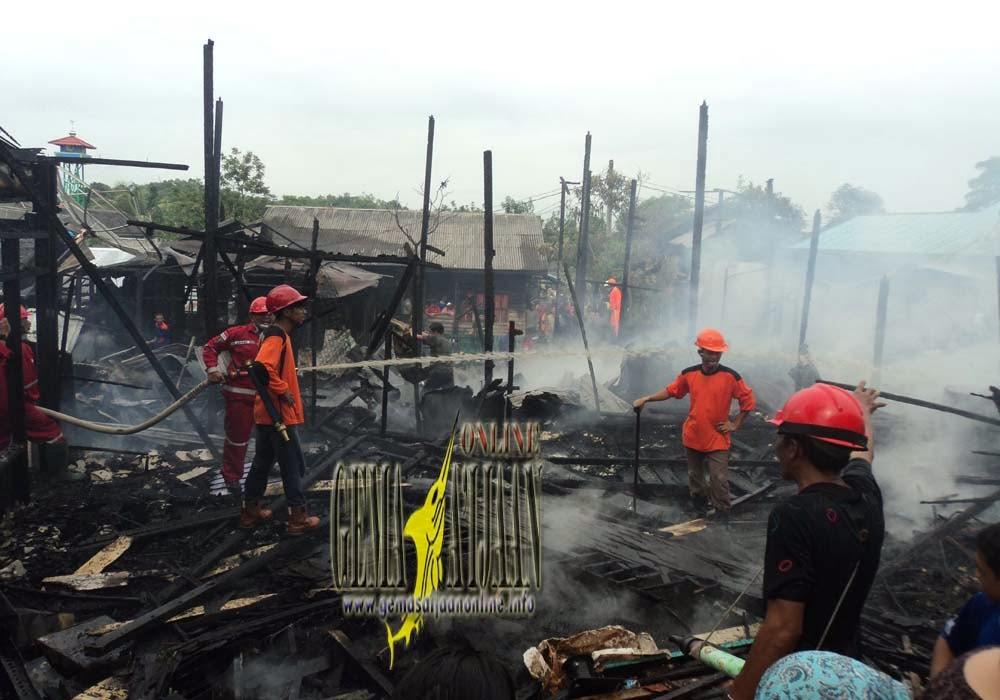 Petugas pemadam kebakaran melakukan pendinginan