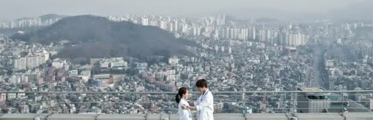 Oh Jin Hee and Oh Chang Min on the roof of the hospital with a view of the city behind them.