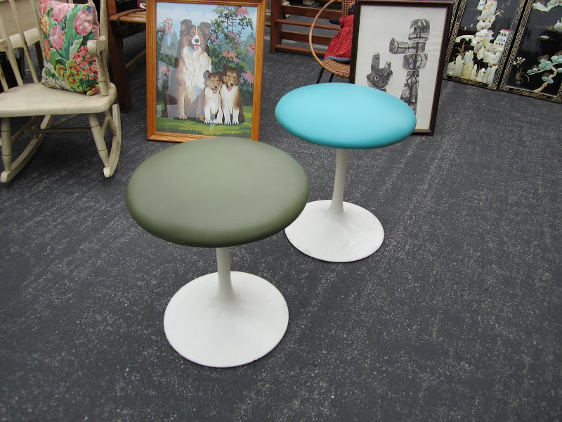 Two Saarinen inspired stools with a white tulip base and vinyl seat cushions