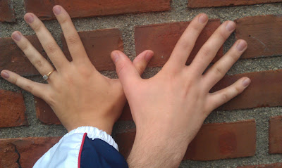 Hands on a brick wall