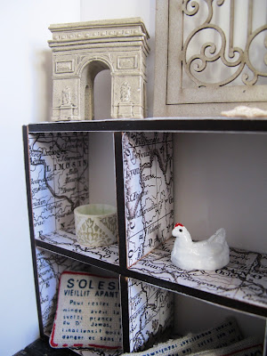 Close-up of one end of a modern dolls' house miniature pigeon hole bookcase, covered in paper printed with a vintage map of France. Displayed on it are a model Arc de triomphe, cushions with french writing on them and a chicken ornament.