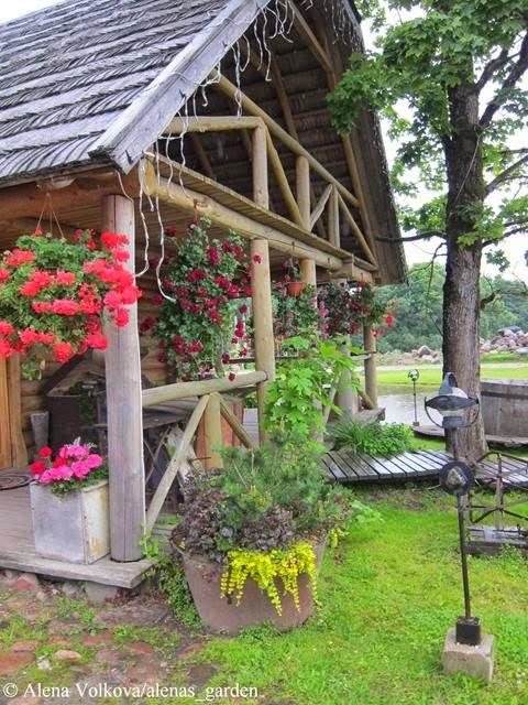 корчма в Литве, деревенский стиль, герань в кашпо, растения в подвесных кашпо, деревянный дом, светильник