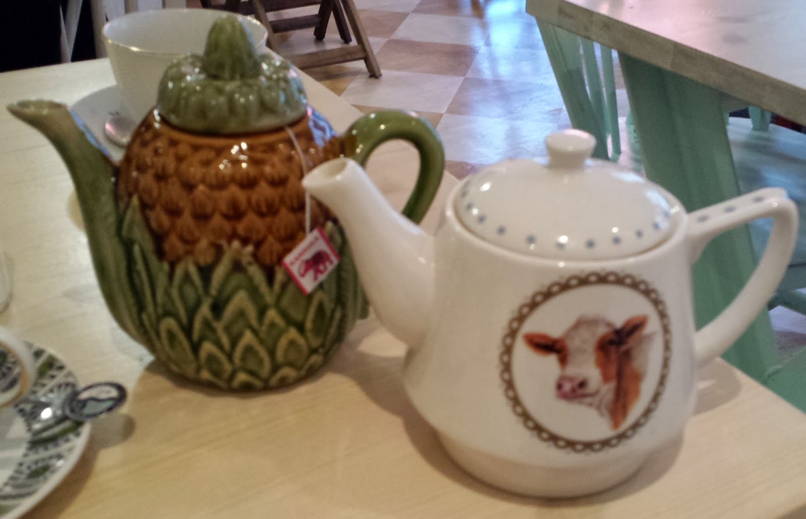 a pineapple teapot and a teapot with a picture of a cow on it
