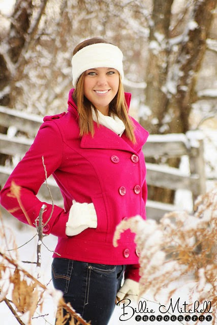 senior girl standing in snowing meadow wearing fushia wool jacket with white headband, scarf, and gloves