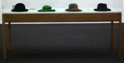 Raised glass case with four women's hats in it, one is bright green, the others dull colors