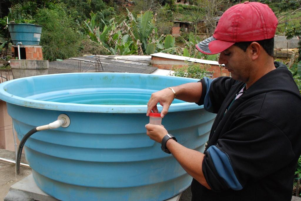 Agente coleta água de caixa d'água destampada e em uso para verificar existência de foco do mosquito Aedes aegypti
