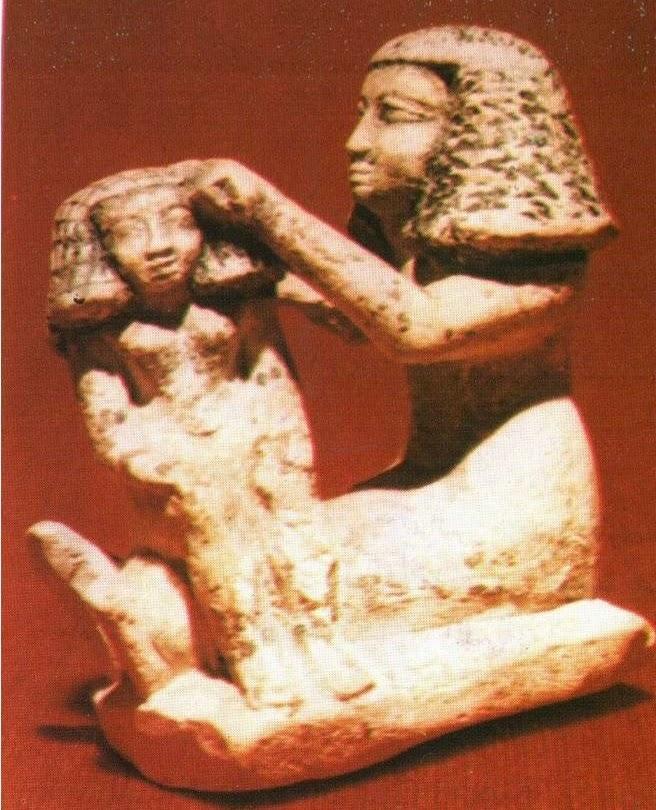 تمثال من الحجر الجيرى يوضح أم تصفف شعر أبنها