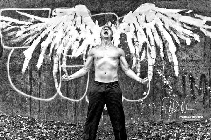 homme torse nu devant ailes blanches peinte sur un mur  philpp bonneau