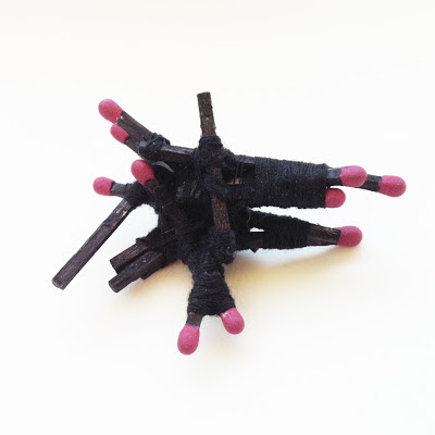 An abstract mini sculpture constructed out of black penned matches and thread.