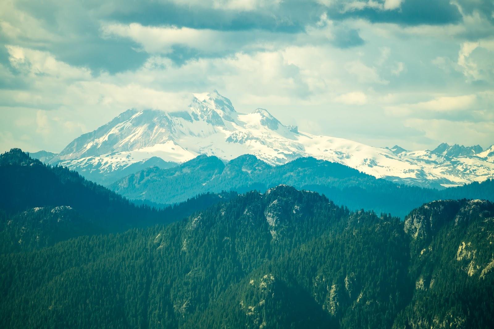 С другой стороны видны заснеженные вершины гор, покоящиеся под мягким одеялом облаков.