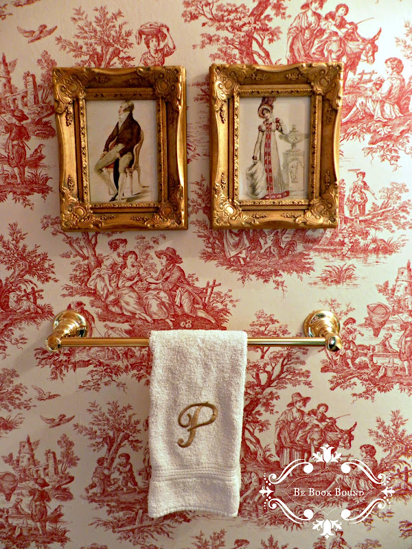 hung these framed prints of Regency era clothing above the towel rack title=