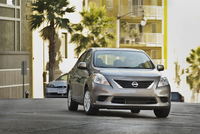 Front three-quarters view of a gray 2012 Nissan Versa being driven on an urban street