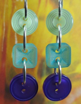 Flattering drop dangle earrings have 3 buttons linked in long strand with silver loops