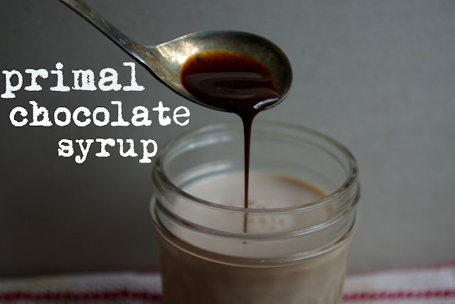 Primal paleo chocolate syrup poured into chocolate milk in a jar with antique spoon