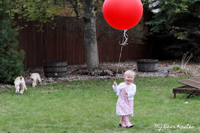Kirsten running around the backyard with her big red balloon on her 2nd birthday