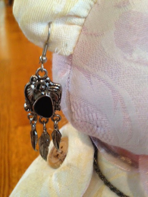 close up of prayer bear wearing dangling earrings