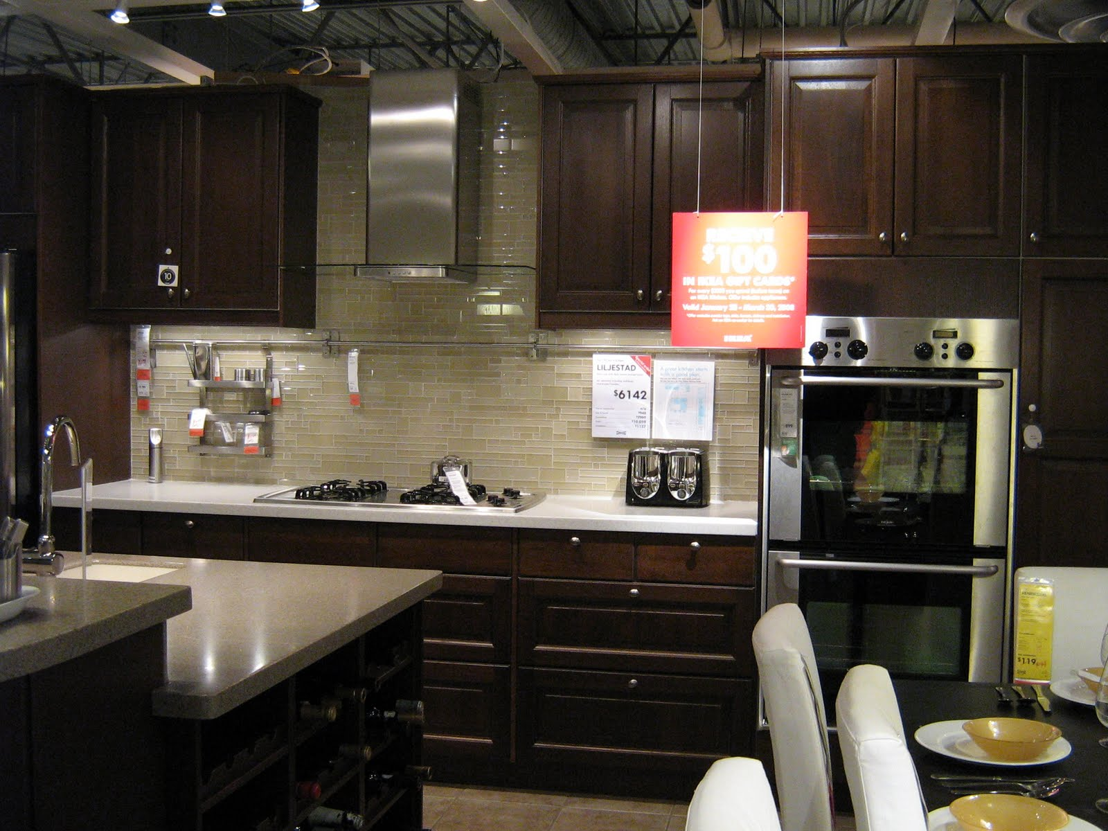 Dark Wood Cabinets And Light Sand Tones Glass Tile Backsplash