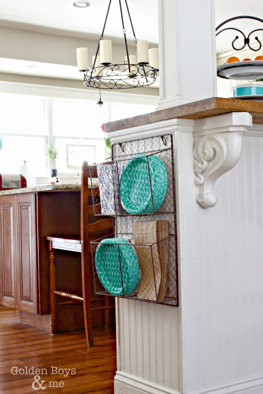 Wire basket hung on cabinet side for storage of paper plates-www.goldenboysandme.com