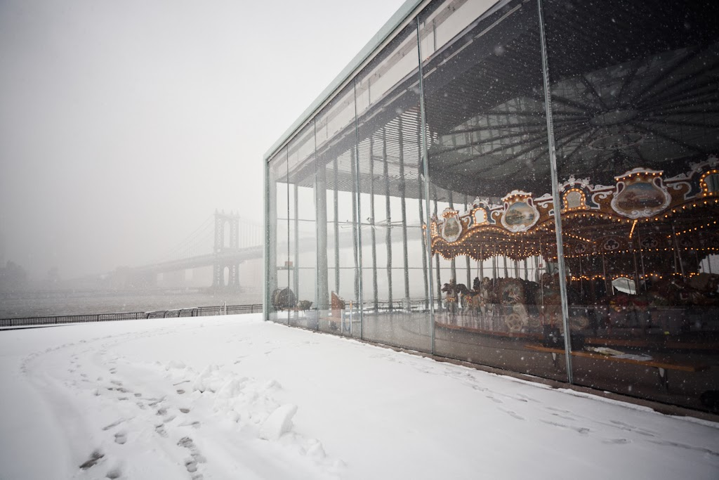 The Dumbo Carousel in it's glass case is a beautiful place to view the snowstorm from, Dumbo, New York