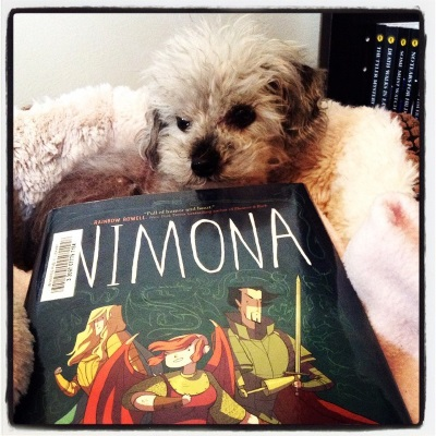 A fuzzy grey poodle, Murchie, curls up inside a high-sided dog bed lined in beige plush. Before him rests a hardcover copy of Nimona. Its cover features an illustration of three people: a blonde white guy in golden armour, a pink-haired white girl with pink wings, and a dark-haired Asian guy with one arm.