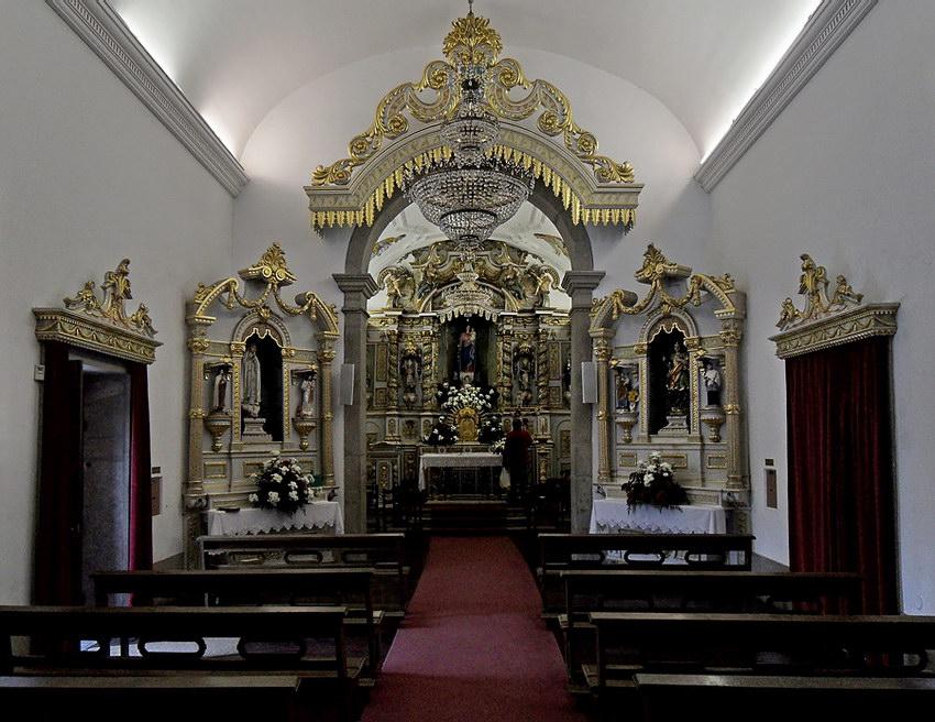 Vista interior, alargada, revelando todo o altar e ainda algumas filas de bancos, embaixo