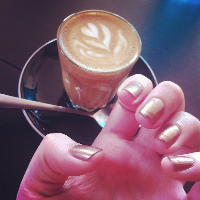 Photo of a piccolo coffee and my hand showing off my light bronze nail polish.