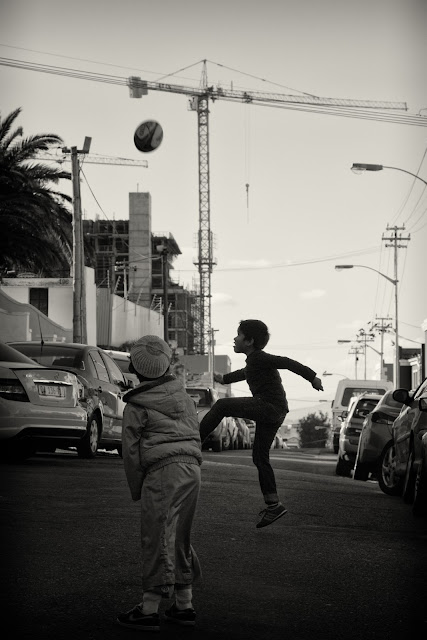 A street photograph taken in the Bokaap of two boys playing Rugby