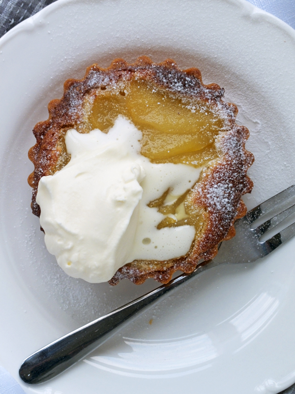 Closer look at a pear frangipane tart with cream and a dessert fork on a white plate.