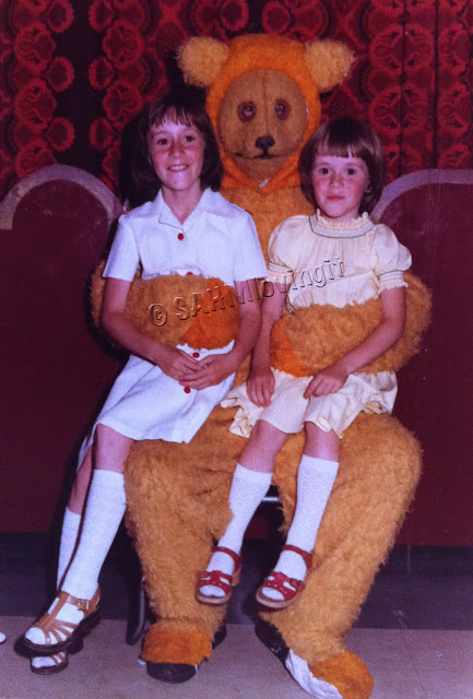 My Sister and I sitting on the lap of a very scary bear