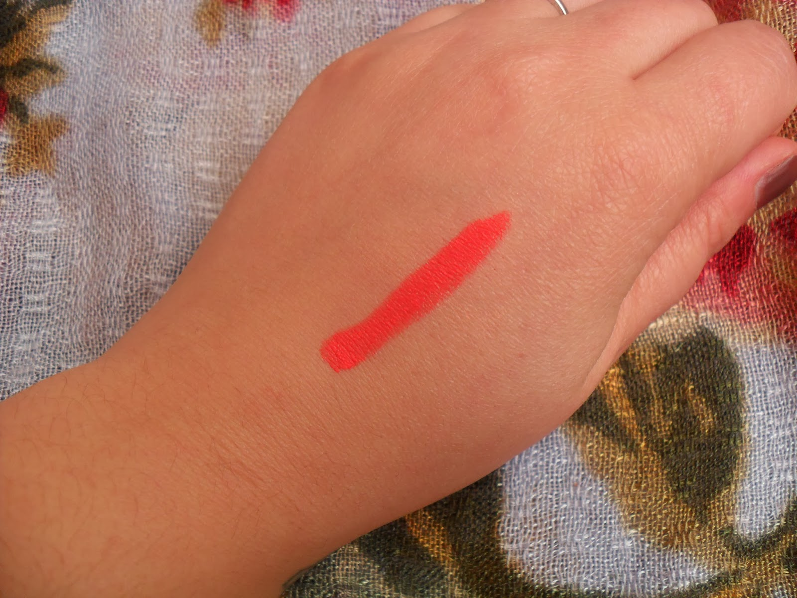 A picture of a Revlon lip product swatch in Audacious