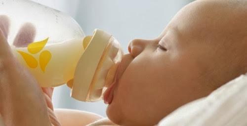 Bebiendo leche materna de las tetas de una madre