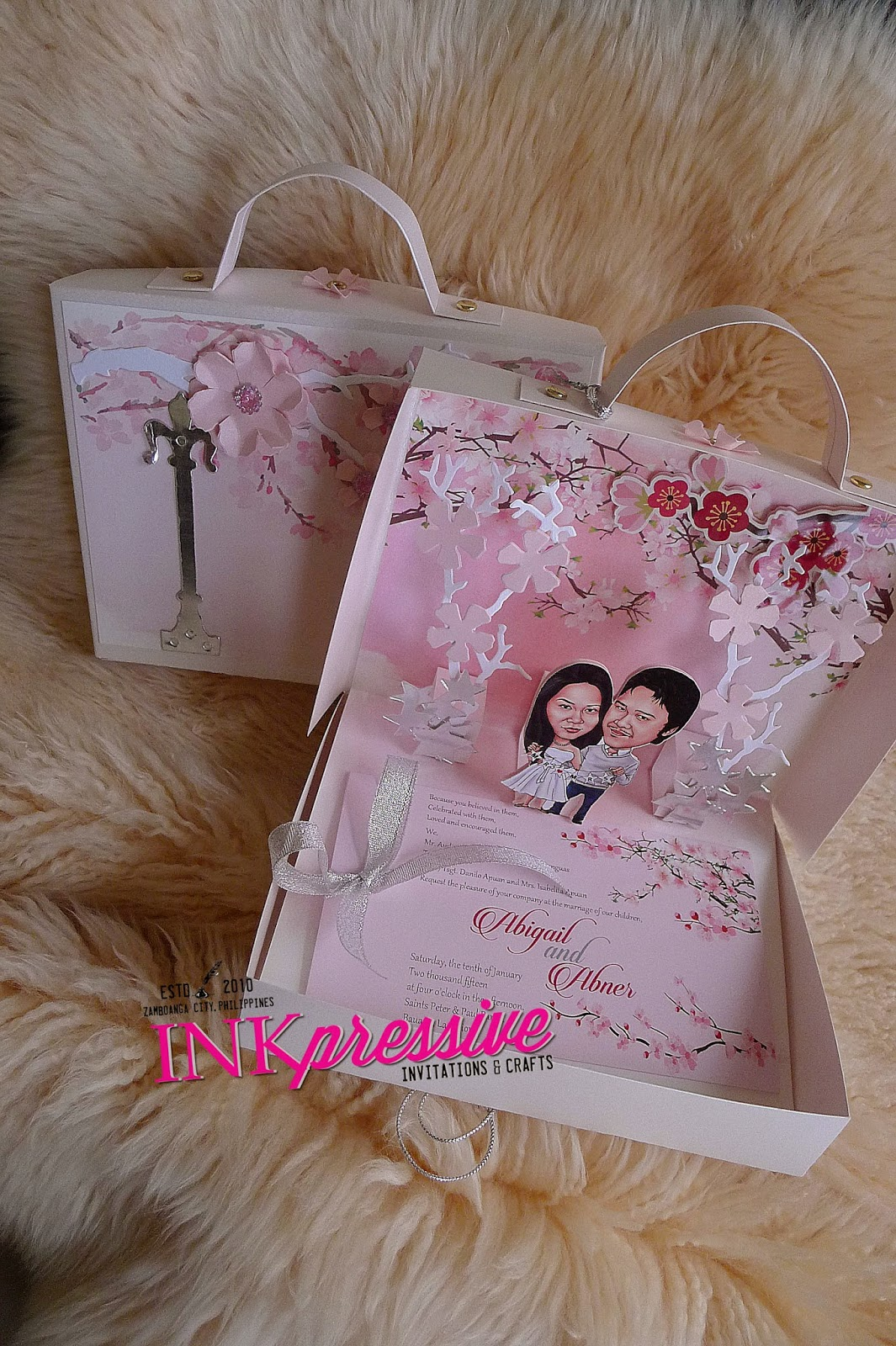 cherry blossom pop up suitcase with caricature wedding invitations