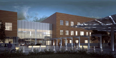 Rendering of front entrance of planned building at dusk.