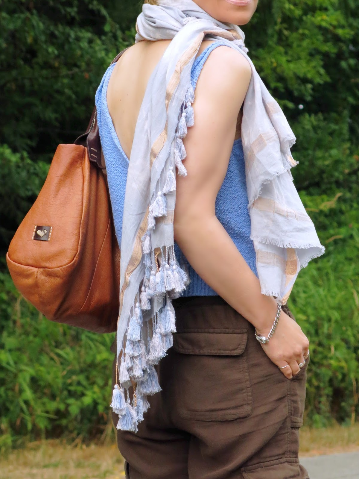styling a knit camisole and slouchy cargo pants with a tasselled scarf