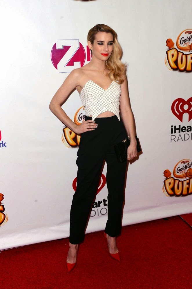 Emma Roberts wears a strapless cropped top and high-waisted trousers to the 2014 Z100s Jingle Ball in New York City