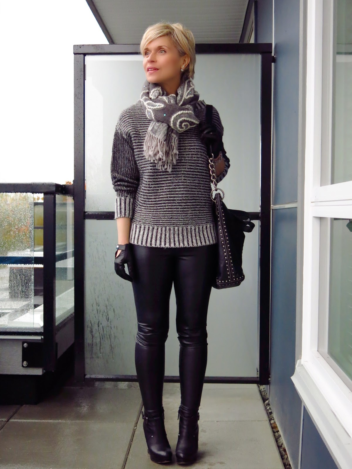 styling faux-leather leggings with a chunky sweater, embroidered scarf, gloves, and wedge booties