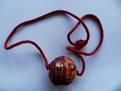 Painted walnut on a string cord