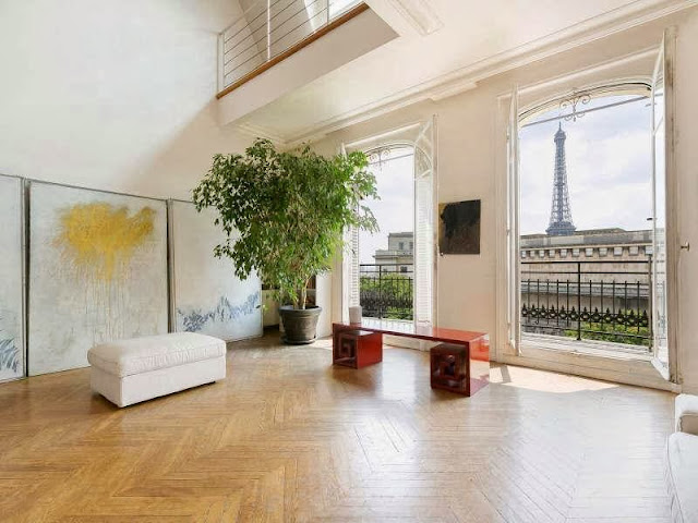 Den in an apartment in Paris, France with herringbone wood floor, french doors with a view of the Eiffel Tower and a Greek key bench