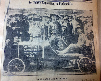 News clipping photo of crowd gathered around man in pushmobile